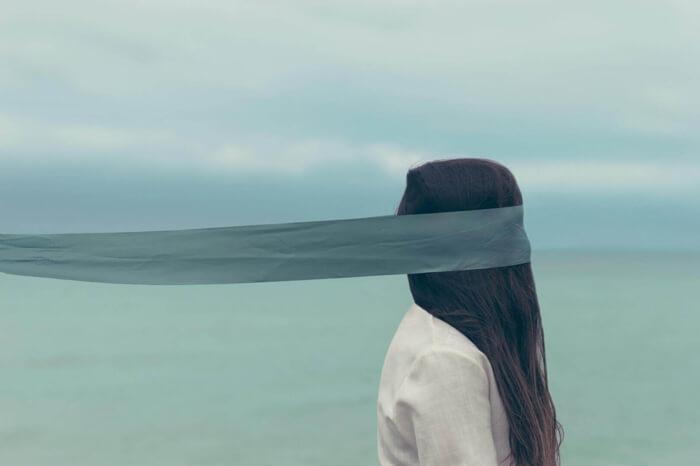 Langhaarige Frau mit Augenbinde